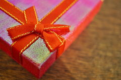 Macro detail of a red ribbon with golden stitching wrapping a pink christmas present Stock Photos