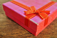 Macro detail of a red ribbon with golden stitching wrapping a pink christmas present Royalty Free Stock Photos