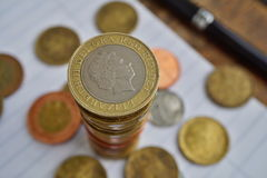 Macro detail of a silver and golden coin in a value of two British Pounds Sterling on the top of coins` pile. In a business background white lined pad, black royalty free stock photos