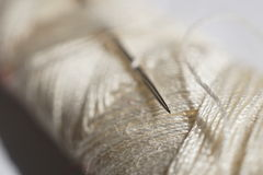 Macro detail of a silver sharp needle inserted in the spool of white thread. Macro detail of silver sharp needle inserted in the spool of white thread royalty free stock photography