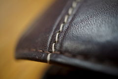 Macro detail of a white thread stitching black and brown stitched leather wallet Royalty Free Stock Photos