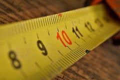 Macro dettaglio del metro del nastro di metallo giallo con i numeri rossi e neri che misurano lunghezza nei centimetri Fotografie Stock Libere da Diritti