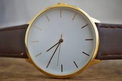 Macro dettaglio di un orologio dorato lussuoso con un quadrante bianco sui precedenti di legno come un simbolo di e orologio cost Fotografia Stock Libera da Diritti