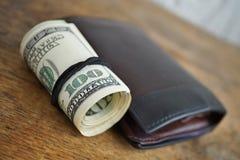Macro dettaglio di un rotolo verde di valuta americana USD, dollari americani con 100 dollari di banconota accanto ad un portafog Fotografia Stock Libera da Diritti