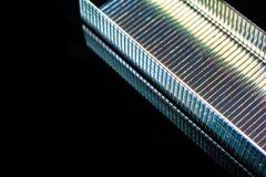 Macro di Staples con una riflessione in un fondo di vetro nero Fotografie Stock Libere da Diritti