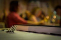 Macro di una forcella sulla tavola con un libro immagine stock libera da diritti