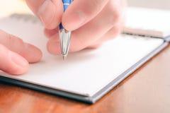 Macro di una scrittura maschio della mano in un organizzatore in bianco With un biro immagine stock libera da diritti