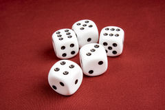 Macro of Dice with shallow depth of field. Macro of five dice on cloth red surface with shallow depth of field focusing on the front dice Stock Images