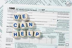 Macro dichte omhooggaand van IRS van 2017 vorm 1040 met KUNNEN WIJ brieven HELPEN Stock Foto