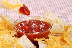 Macro dipping nachos and cheese in salsa Stock Photography
