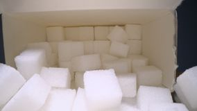 Macro dolly shot of gliding through sugar cubes next into carton box on wooden table. Unhealthy food sweetener, sweet crystal cube. S stock footage