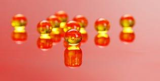 Macro of E vitamine pills on red. Macro of shiny, yellow E vitamin balls on red background Royalty Free Stock Image