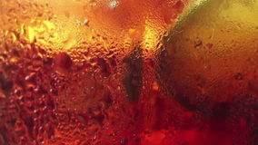 Macro ECU of a slice of lime resting amongst bubbles in a color-colored fizzy stock footage