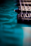 Macro Electric Guitar Strings & Metallic Paint. A tight artistic macro close up with very shallow depth of field, of electric guitar strings & teal metallic Stock Photo