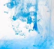 Macro, estratto La pittura blu dell'acquerello cade in acqua con fondo bianco immagine stock