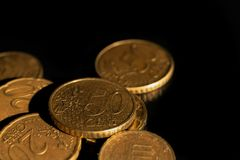 Macro euro coins in a pile. A macro shot of euro coins in a pile from the side on a black background stock photos