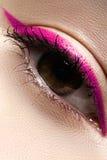 Macro eye with fashion bright eyeliner make-up. Elegance close-up of beautiful female eye with fashion trend bright colors eyeshadow and eyeliner. Macro shot of stock images