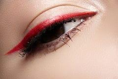 Macro eye with fashion bright eyeliner make-up. Elegance close-up of beautiful female eye with fashion trend red eyeshadow and eyeliner. Macro shot of beautiful royalty free stock photography