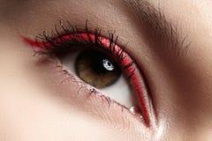 Macro eye with fashion bright red eyeliner make-up. Elegance close-up of beautiful female eye with fashion trend red eyeshadow and eyeliner. Macro shot of royalty free stock photo