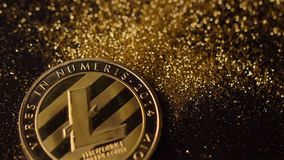 Glowing Litecoin Falls down on Gold Sparkles Macro stock footage