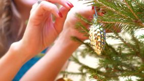 Macro hands hang fir toy cone on new year tree slow motion. Macro female hands with red manicure and luxury ring hang golden fir toy cone on new year tree in stock footage