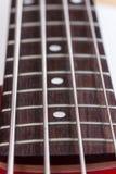 Macro ficelles étroites de cou de frettes de bas de guitare images stock