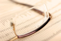 Macro of financial data and eyeglasses. Royalty Free Stock Image