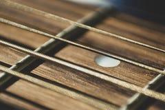 Macro fine sul colpo delle corde della chitarra acustica su lustro del sole Musica fotografie stock libere da diritti