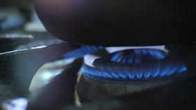 Macro flashes de flamme de gaz sous la grande casserole sur le brûleur de fourneau banque de vidéos