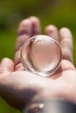 Macro foto del globo di vetro in mano umana Fotografie Stock