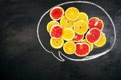 Macro foto dell'alimento art Fette della frutta su un fondo scuro della lavagna messaggio Fotografia Stock