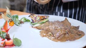 Macro foto dell'alimento art Il cuoco unico aggiunge il pepe al piatto con fegato e le bacche in caramello sauce Movimento lento stock footage