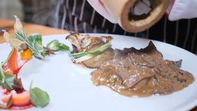 Macro foto dell'alimento art Il cuoco unico aggiunge il pepe al piatto con fegato e le bacche in caramello sauce Movimento lento archivi video