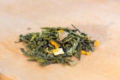 Macro foto di tè La composizione del mucchio del fiore secco dell'ibisco situato su un bordo di legno Tè naturale verde Fotografia Stock