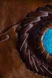Macro fragment of a leather bag or purse. Handmade, texture background. Brown natural leather, concentric stripes and turquoise stone. Macro fragment of a Stock Photo