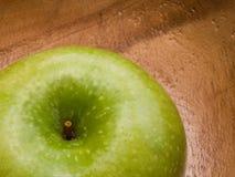 Macro of fresh green apple on wooden dish Royalty Free Stock Photo
