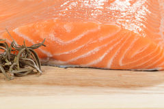 Macro fresh salmon and dried rosemary. On wood cutting board Royalty Free Stock Photos