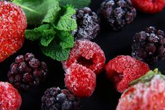 Macro frozen raspberry, blackberry, strawberries mint leaves, on a black shale board, frozen fruit, set.  Royalty Free Stock Photo
