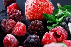 Macro frozen raspberry, blackberry, strawberries mint leaves, pieces of ice on a black shale board, frozen fruit, set.  Stock Photos