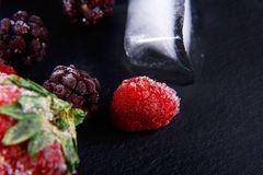 Macro frozen raspberry, blackberry, strawberries mint leaves, pieces of ice on a black shale board, frozen fruit, set.  Stock Photo