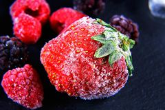 Macro frozen raspberry, blackberry, strawberries mint leaves, pieces of ice on a black shale board, frozen fruit, set.  Royalty Free Stock Photo