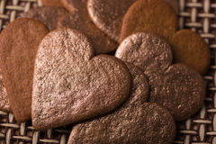 Macro gingerbread hearts heaped out with gold hearts. On cane background Royalty Free Stock Photo