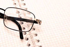 Macro of glasses notebook. Soft light vintage style Stock Image