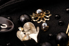 Macro golden flower and black beads on fabric Stock Photos