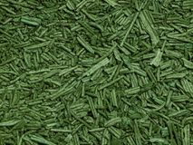 Spirulina background. Macro of green dry spirulina flakes used as food supplement rich of vitamins, antioxidants and minerals Stock Photo