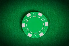 Macro green poker chip on table. One macro green poker chip on table royalty free illustration