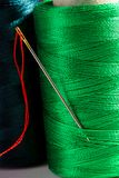 Macro green spool of thread with needle Royalty Free Stock Photography