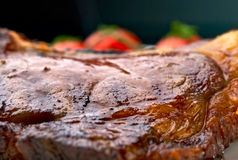 Macro of grilled meat ribs on white plate. Club Steak. Veal on the bone. Macro of grilled meat ribs on white plate with cherry tomatoes and dark hot sauce Stock Photography