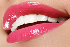Macro happy woman's smile with healthy white teeth, bright pink. Lips make-up. Stomatology and beauty care. Woman smiling with great teeth. Cheerful female Royalty Free Stock Photo