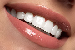 Macro happy woman`s smile with healthy white teeth.Lips make-up. Stomatology and beauty care. Woman smiling with great teeth. Cheerful female smile with fresh Royalty Free Stock Photos